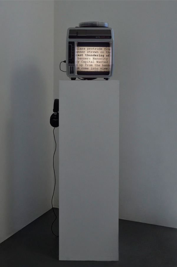 "Tris Vonna-Michell,   Prelude: Capitol Complex,   2013,   Telex projector on plinth,   80 slides,   sound-work on headphones / proiettore Telex su plinto,   80 diapositive,   lavoro audio in cuffia,   6? 38"" - Courtesy T293,   Napoli - Roma"