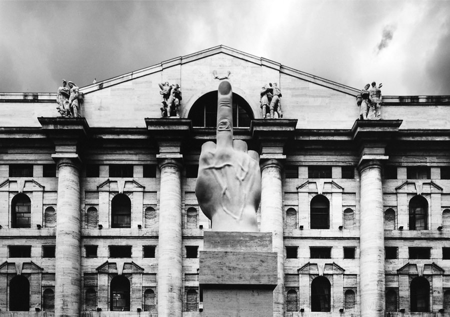 """""""L.O.V.E."""" by Maurizio Cattelan placed in Piazza Affari in Milan. Palazzo Mezzanotte,   the stock exchange headquarters,   is a hallmark of Fascist architecture. As it's placed,   it points away from the stock exchange,   and not at it."""""""