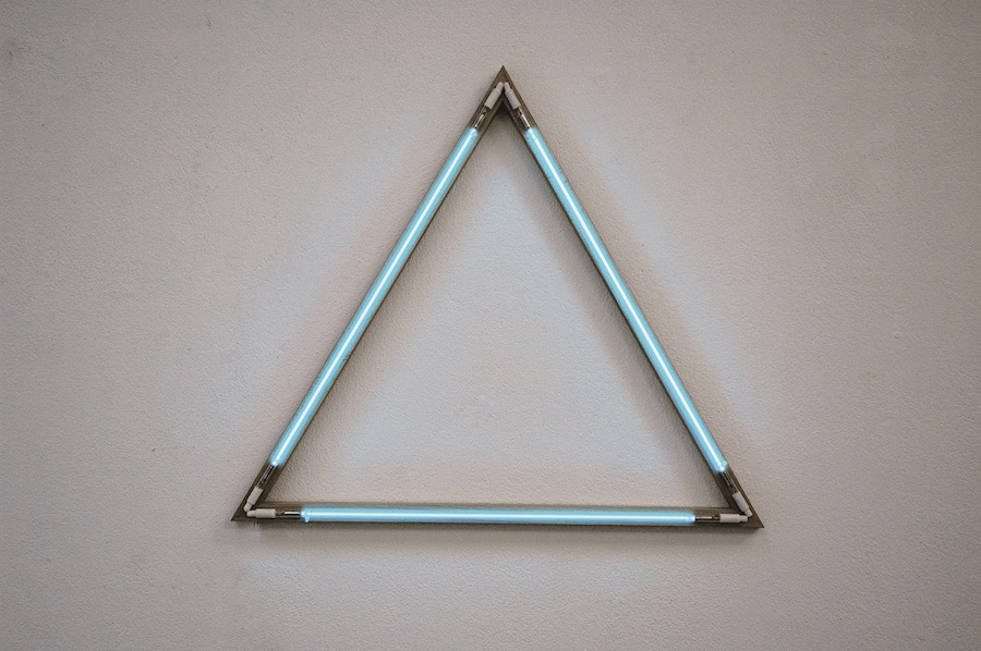 FRANÇOIS MORELLET TRIANGLE ÉQUILATÉRAL,   NÉONS BLEUS INTERFÉRENTS,   1973 THREE BLUE ARGON PIPES ON WOOD 78 X 90 CM COURTESY FRANÇOIS MORELLET AND GALERIE CATHERINE ISSERT,   SAINT PAUL DE VENCE
