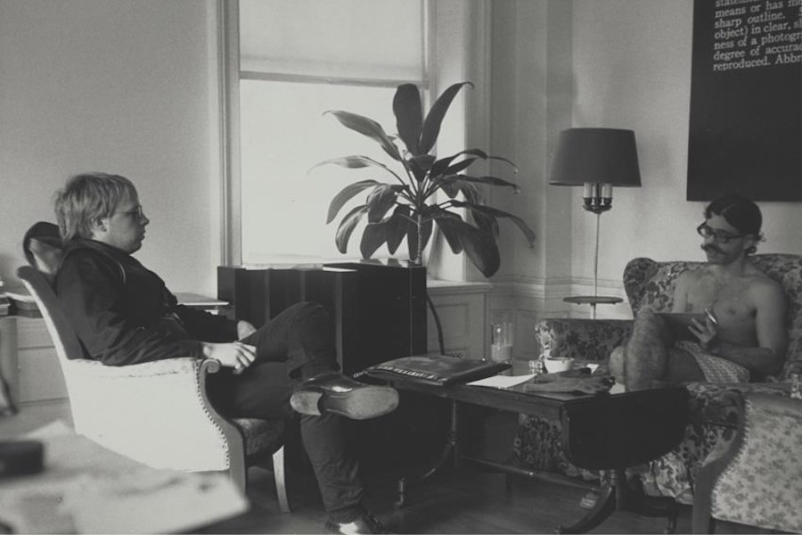 "At left,   Joseph Kosuth with Seth Siegelaub; ""Titled (Art as Idea as Idea) The Word 'Definition,  '"" 1966-1968,   by Joseph Kosuth installed above sofa,   c. 1960s-1970s. New York,   Museum of Modern Art (MoMA)."