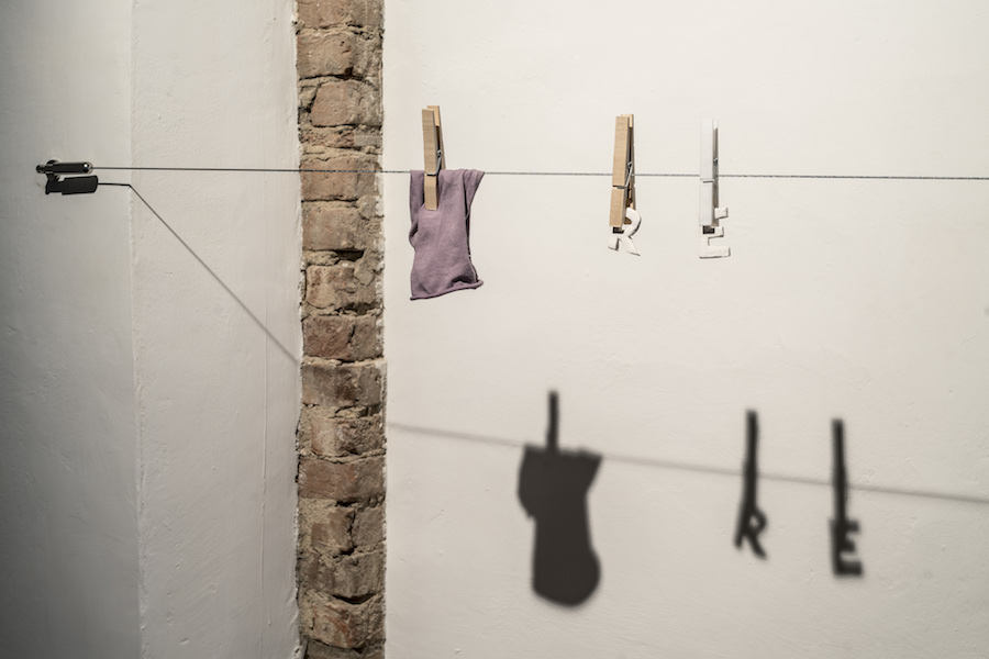 Rosa Aiello, Filo da bucato (re), 2017, (part.). Steel wire, steel hardware, clothespins, socks, porcelain. Ph OKNOstudio.